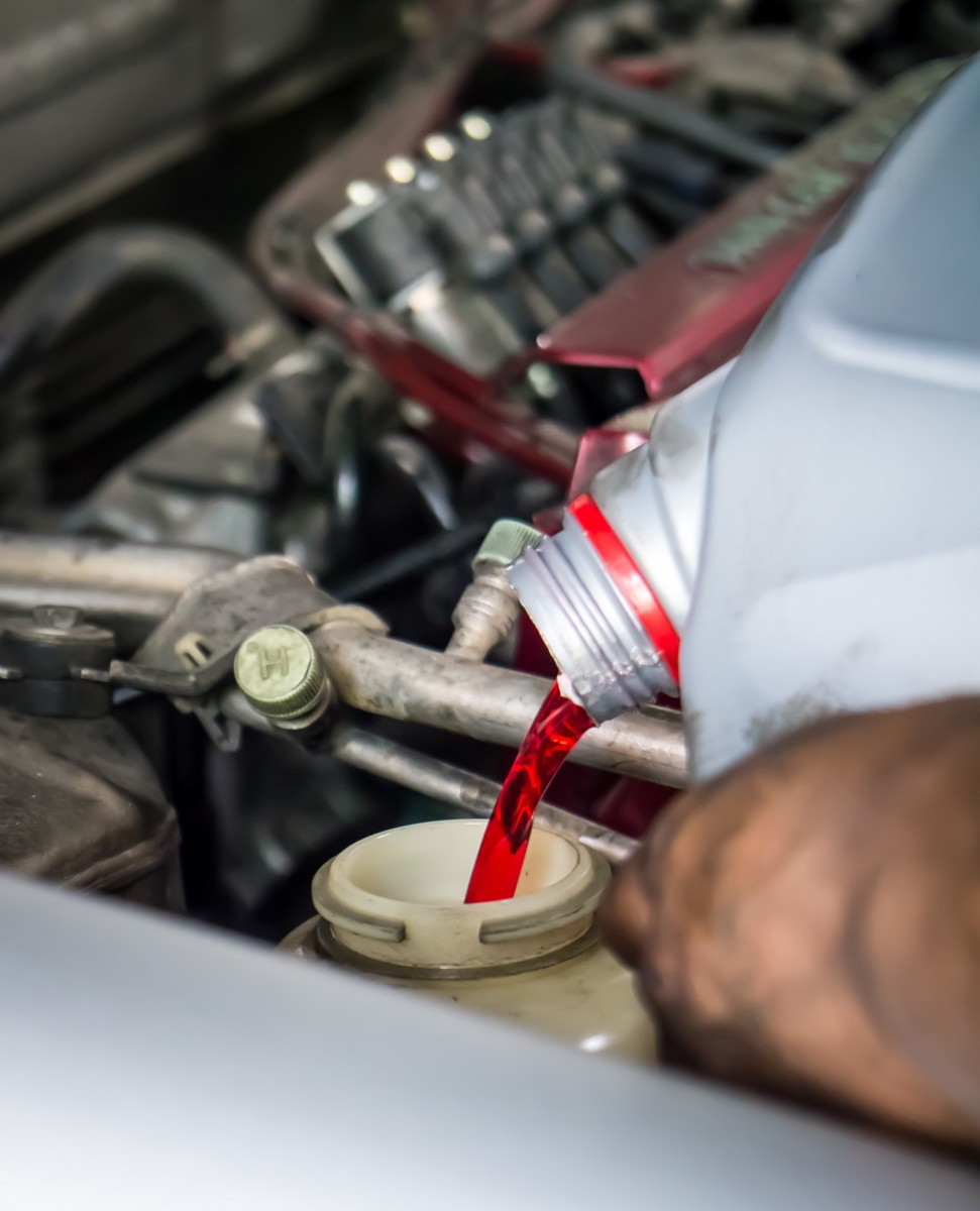 transmission fluid being poured into car